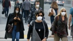 FILE - In this Nov. 9, 2018, file photo, people wear masks while walking through the Financial District in the smoke-filled air in San Francisco. (AP Photo/Eric Risberg, File)