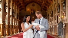 Prince Harry, Duke of Sussex (R), and his wife Meghan, Duchess of Sussex, pose with their newborn baby son, Archie Harrison Mountbatten-Windsor, in St George's Hall at Windsor Castle. (AFP)
