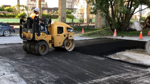 A crew is seen filling a pothole on Martin Goodman Trail on June 25, 2019.