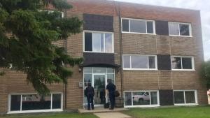 Members of the Saskatoon Police Service enter an apartment unit at 602 Hopkins Street Tuesday, June 25 following a homicide on Monday. (Laura Woodward/CTV Saskatoon)