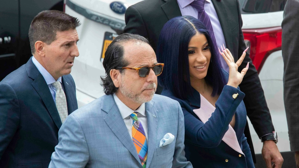 Grammy-winning rapper Cardi B, right, waves at fans as she arrives for a hearing at Queens County Criminal Court, Tuesday, June 25, 2019, in New York. (AP Photo/Mary Altaffer)