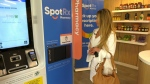 A woman stands next to the new SpotRX drug dispensing machine in the GTA.