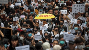 Protesters with an umbrella stage a protest outside the European Union office in Hong Kong, Wednesday, June 26, 2019. (AP Photo/Kin Cheung)