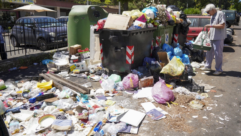 A man stands by uncollected garbage in Rome, on June 24, 2019. (Andrew Medichini / AP)