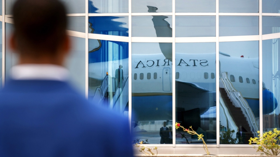 A member of Diplomatic Security stands guard on the tarmac as the plane for U.S. Secretary of State Mike Pompeo is reflected in a glass building in Abu Dhabi, United Arab Emirates, on June 25, 2019. (Jacquelyn Martin / AP)