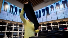 An employee folds yoga pants as the types of pants are animated and displayed on digital screens instead of mannequins at a Lululemon Athletica store in Vancouver on August 21, 2014. Lululemon Athletica Inc. wants customers to have more pea in their yoga pants.The athleisure retailer presented the idea at Protein Industries Canada's (PIC) pitch day Monday in a talk titled: Clothing the World with Crops, according to a photo of a PowerPoint slide. THE CANADIAN PRESS/Darryl Dyck