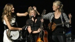 Emily Robison, left, and Martie Maguire, right, adjust Natalie Maines' hair as the Dixie Chicks perform at the new Nokia Theatre in Los Angeles, on Oct. 18, 2007. (Gus Ruelas / AP)