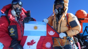Horacio Galanti, left, poses with Ang Mingma, right, atop Mount Everest with the flags of Argentina, Canada, and Tibet. (Courtesy: Horacio Galanti)