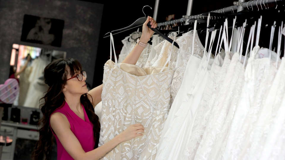 Photo Assistant manager Brooke Hernandez hangs wedding gowns Friday, June 21, 2019 at Strut Bridal Shop in Tempe, Ariz. (AP Photo/Matt York)