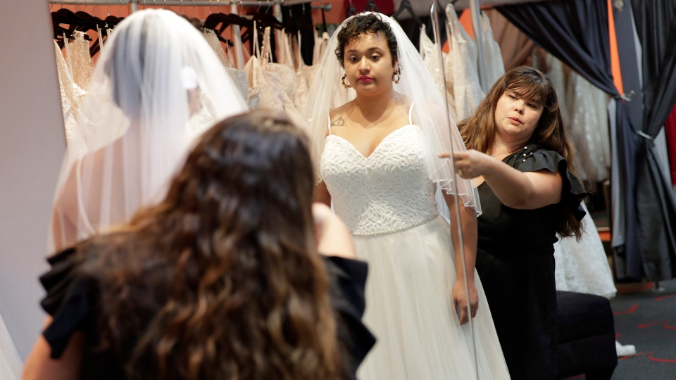 Ann Campeau,, right, owner of Strut Bridal, fits a new dress on inventory manager Stefanie Zuniga at her shop in Tempe, Ariz. (AP Photo/Matt York)