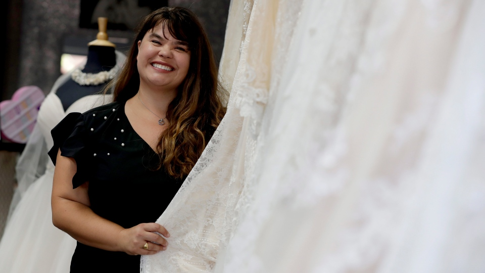 In this Friday, June 21, 2019, photo Ann Campeau, owner of Strut Bridal, stands in her shop in Tempe, Ariz. (AP Photo/Matt York)