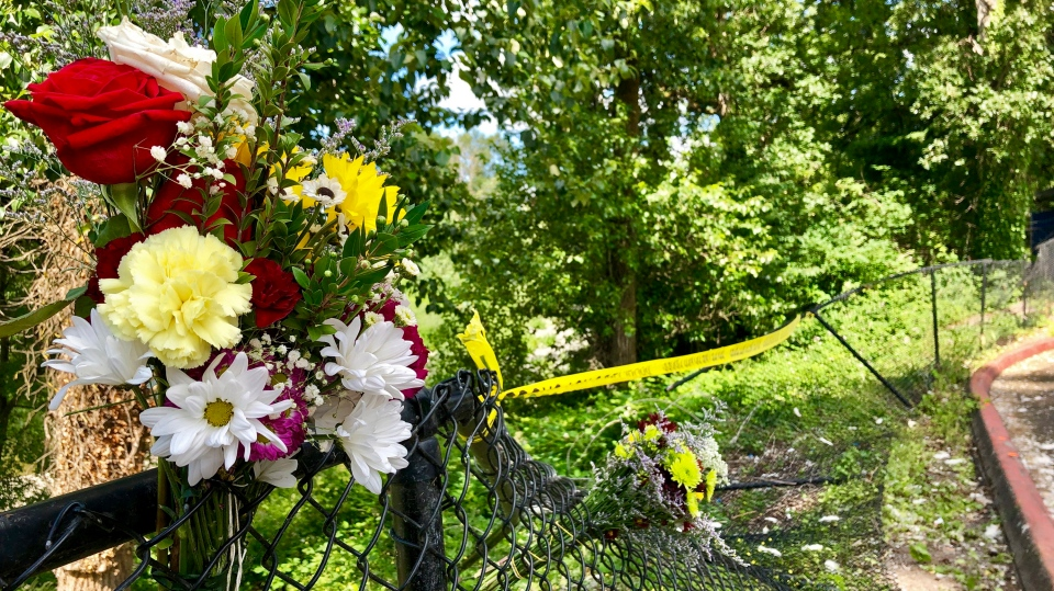 Bouquets of flowers sit on a fence on Wednesday, June 26, 2019, that was knocked down when a driver crashed into a swimming hole in Washougal, Wash., and ran over two German tourists who were sunbathing by the Washougal River, killing them. (AP Photo/Gillian Flaccus)
