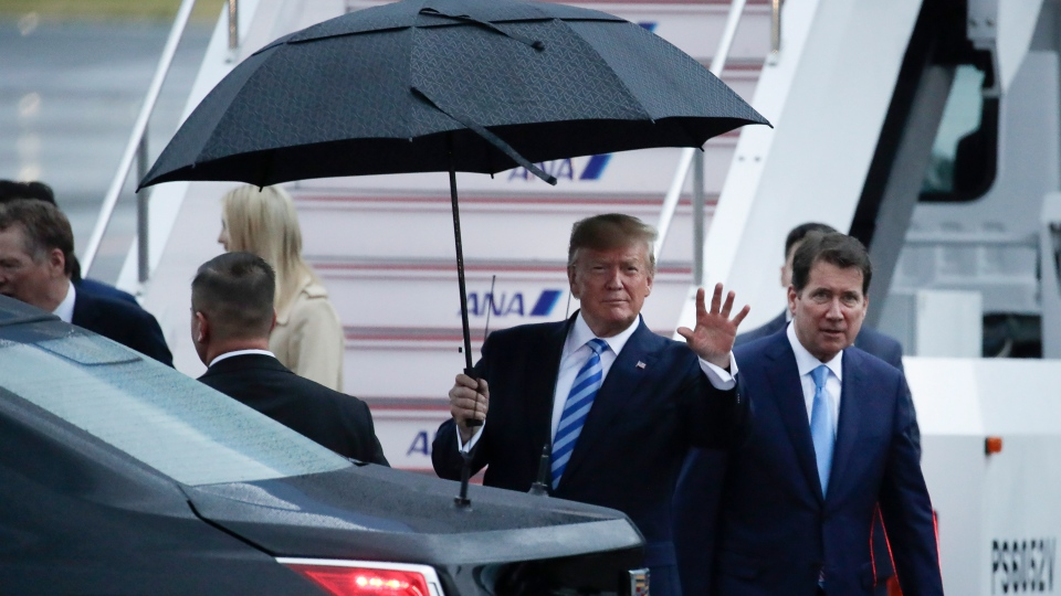 U.S. President Donald Trump waves toward the media after arriving at the Osaka International Airport to attend the G-20 Summit Thursday, June 27, 2019, in Osaka, Japan. (AP Photo/Jae C. Hong)