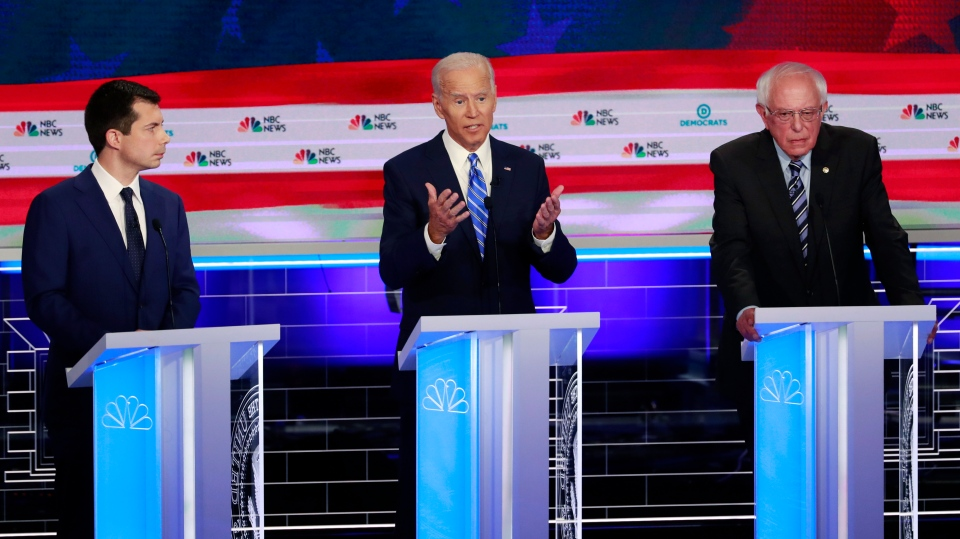 Democratic presidential candidate former vice president Joe Biden, speaks during the Democratic primary debate hosted by NBC News at the Adrienne Arsht Center for the Performing Arts, Thursday, June 27, 2019, in Miami, as South Bend Mayor Pete Buttigieg, left, and Sen. Bernie Sanders, I-Vt., listen. (AP Photo/Wilfredo Lee)