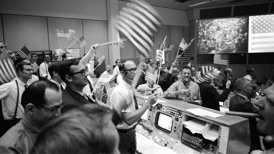 In this July 24, 1969 photo made available by NASA, flight controllers at the Mission Operations Control Room in the Mission Control Center at the Manned Spacecraft Center in Houston, celebrate the successful conclusion of the Apollo 11 lunar landing mission. (NASA via AP)