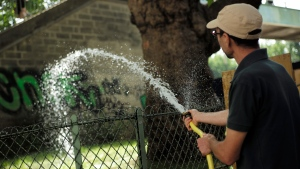 A man uses a hose along the Canal de l'Ourcq in Paris, Friday, June 28, 2019. Schools are spraying kids with water and nursing homes are equipping the elderly with hydration sensors as France battles a record-setting heat wave baking much of Europe. (AP Photo/Lewis Joly)