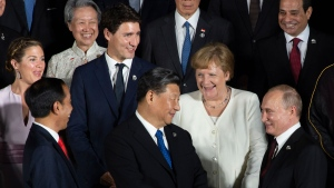 Sophie Gregoire Trudeau, Prime Minister Justin Trudeau, German Chancellor Angela Merkel, Indonesian President Joko Widodo(front left), Chinese President Xi Jinping and Russian President Vladimir Putin share a laugh as they wait for a photo at the G20 Summit in Osaka, Japan, Friday June 28, 2019. THE CANADIAN PRESS / Adrian Wyld