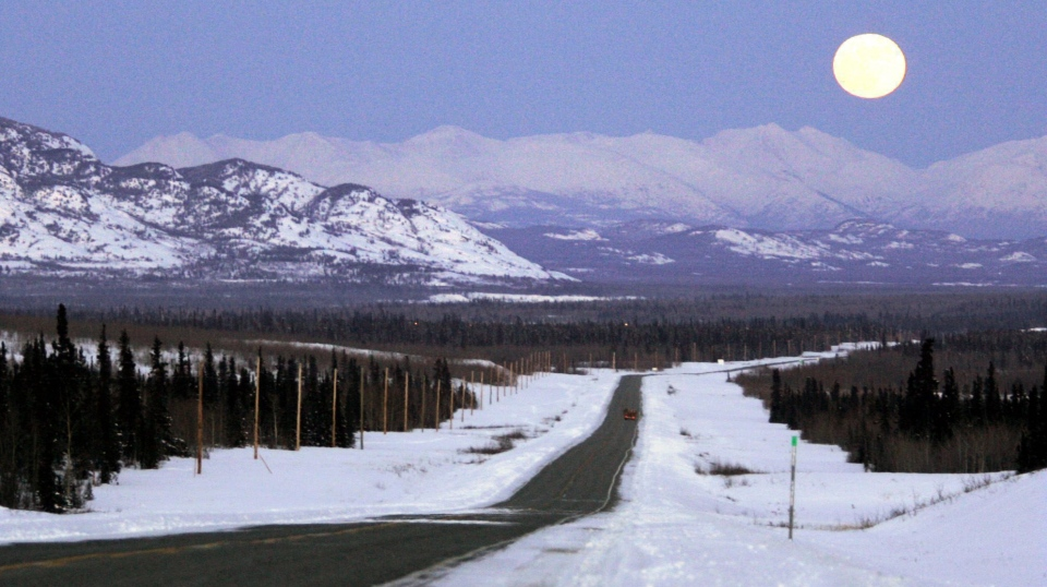 The moon rises over mountains along the Alaska Highway heading west to Whitehorse in the Yukon on March 4, 2007. (The Canadian Press/Chuck Stoody)