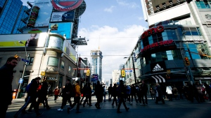 People walk around cross the street at Yonge and Dundas in Toronto, on Wednesday, Nov. 14, 2012. (THE CANADIAN PRESS/Nathan Denette)