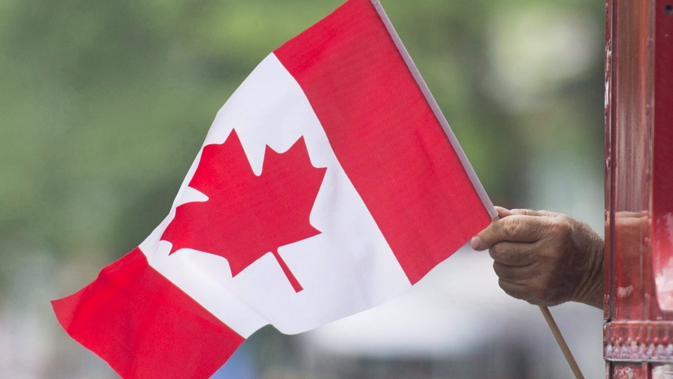 A man waves a flag during a Canada Day parade in Montreal, on July 1, 2018. (THE CANADIAN PRESS/Graham Hughes)