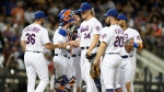New York Mets' manager Mickey Callaway (36) takes the ball from starting pitcher Noah Syndergaard (34) as teammates surround their starter during the sixth inning of a baseball game against the Atlanta Braves, Sunday, June 30, 2019, in New York. (AP Photo/Kathy Willens)
