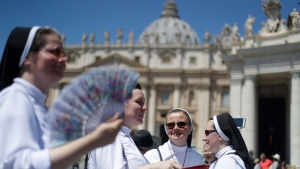 Nuns hold fans to cool-off in St. Peter's Square, at the Vatican, Sunday, June 30, 2019. Pope Francis is recalling those who have particularly suffered in the current heat wave, including those who work outdoors. The pope told the public in St. Peter's Square Sunday that he wished all workers a period of rest during the summer that would be good for both them and their families. (AP Photo/Gregorio Borgia)