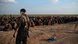 In this Feb. 22, 2019 file photo, U.S.-backed Syrian Democratic Forces (SDF) fighters stand guard next to men waiting to be screened after being evacuated out of the last territory held by Islamic State group militants, near Baghouz, eastern Syria. (AP Photo/Felipe Dana, File)