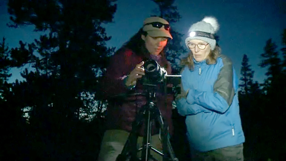Instructor Lisa Kinnear, left, gives some tips during a nighttime photography seminar in the Crowsnest Pass.