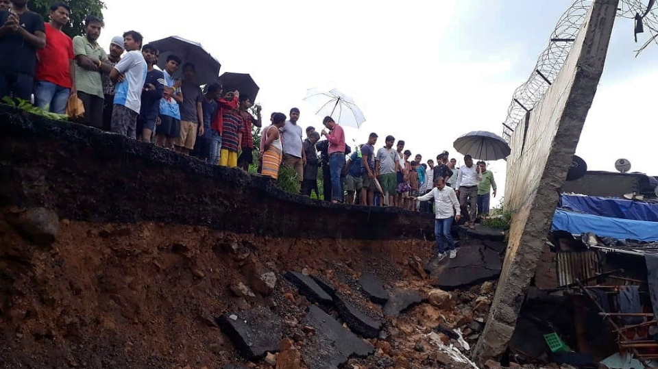Rescuers and onlookers stand at the spot of a wall collapse in Mumbai, India, Tuesday, July 2, 2019. Nearly a dozen people are feared killed. (AP Photo/Rafiq Maqbool)