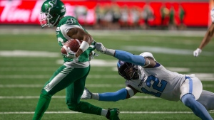 Saskatchewan Roughriders wide receiver Christion Jones (22) runs the ball as Toronto Argonauts linebacker Nelkas Kwemo (12) grabs onto his jersey during second half CFL football action in Regina on Monday, July 1, 2019. THE CANADIAN PRESS/Kayle Neis