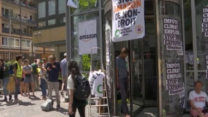 Environmental activists mount a passive protest targeting the Amazon headquarters building in Paris, France, Tuesday July 2, 2019, accusing the online distribution company of destroying jobs and hurting the planet. (AP Photo)