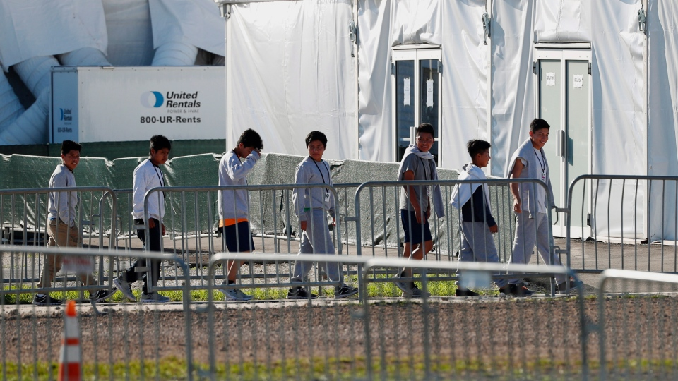 In this Feb. 19, 2019 photo, youngsters line up to enter a tent at the Homestead Temporary Shelter for Unaccompanied Children in Homestead, Fla. (AP Photo/Wilfredo Lee, File)