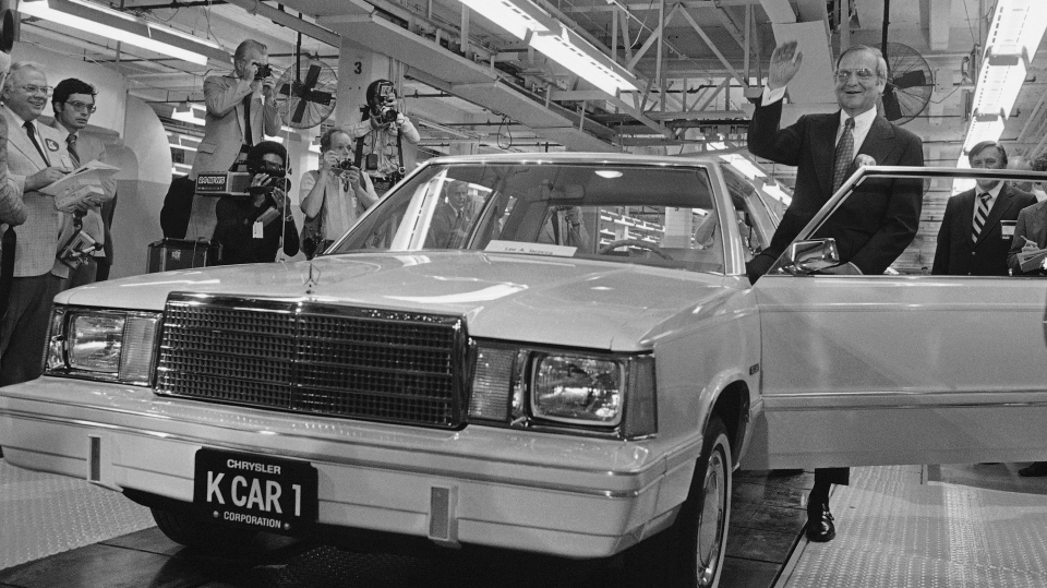 In this Aug. 6, 1980, file photo, Chrysler Chairman Lee Iacocca, right, waves as he steps into the first K-Car at ceremonies in Detroit, Mich.  (AP Photo/Dale Atkins, File)