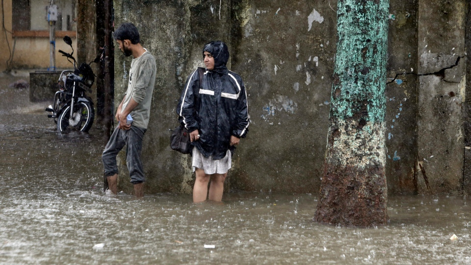 People wade through a waterlogged street following heavy rains in Mumbai, India, Tuesday, July 2, 2019. (AP Photo/Rajanish Kakade)