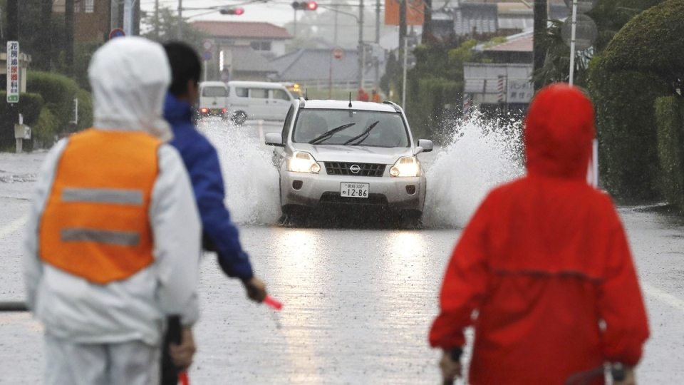 A car drives through a flooded road during heavy rain on July 3, 2019, in Miyakonojo City, Miyazaki Prefecture, southwest Japan.  (Kyodo News via AP)