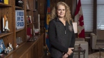 Gov. Gen. Julie Payette stands next to a shelf featuring memorabilia from her career as an astronaut, in her office at Rideau Hall in Ottawa on December 11, 2018. THE CANADIAN PRESS/Justin Tang
