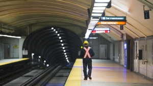 A Montreal Metro maintenance worker walks along a station platform during the early hours of the morning in Montreal, Thursday, April 11, 2019. THE CANADIAN PRESS/Graham Hughes