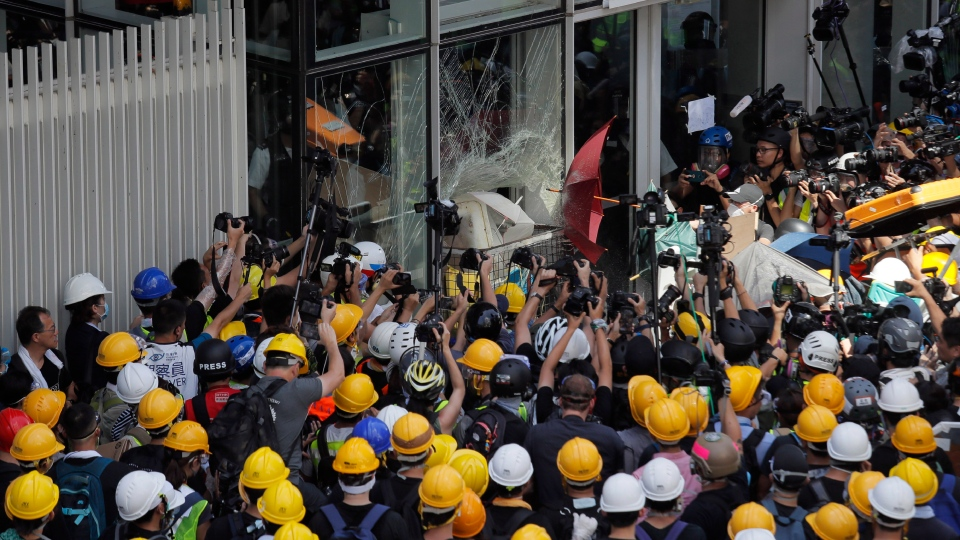 In this photo taken July 1, 2019, protesters use a cart to break through the glass panel of the Legislative Council in Hong Kong. (AP Photo/Kin Cheung)