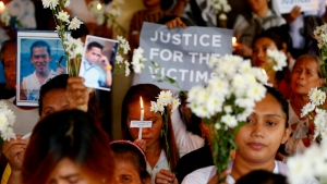 In this March 17, 2019, file photo, relatives of victims in President Rodrigo Duterte's so-called war on drugs hold a memorial for their loved ones at a church in Manila, Philippines. On Thursday, July 4, 2019, the Commission on Human Rights has condemned the killing of a three-year-old girl in a crossfire in a Philippine police raid in which her father, a drug suspect, was gunned down along with another civilian and a police officer. (AP Photo/Bullit Marquez, File)