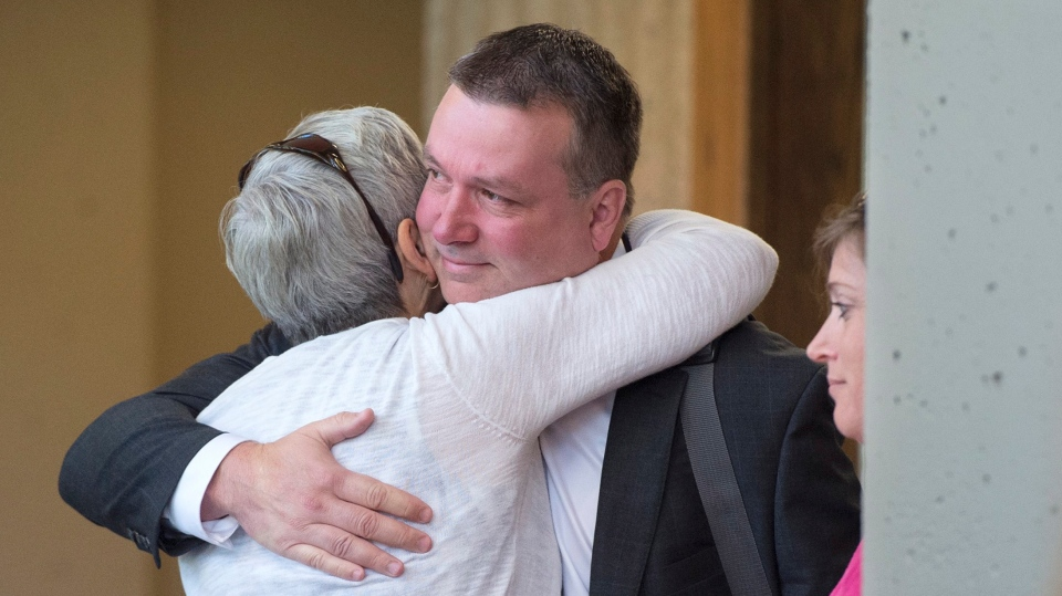 Craig Robert Burnett, a former senior Nova Scotia Mountie convicted of stealing 10 kilograms of cocaine from an exhibit locker, is greeted by family and friends as he arrives for sentencing at Nova Scotia Supreme Court in Halifax on Thursday, July 4, 2019. (THE CANADIAN PRESS/Andrew Vaughan)