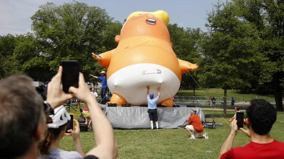People photograph a Baby Trump balloon as it is moved into position before Independence Day celebrations, on July 4, 2019. (Patrick Semansky / AP)