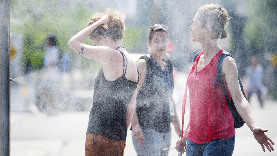 People use misters to cool down during a heatwave in Montreal, on July 2, 2018. THE CANADIAN PRESS/Graham Hughes