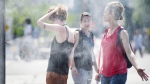 People use misters to cool down during a heatwave in Montreal, on July 2, 2018. Montreal's mayor is unveiling the city's plan to respond to heatwaves after dozens of people died amid high temperatures last summer.THE CANADIAN PRESS/Graham Hughes