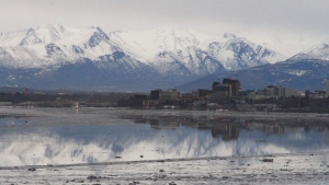 This Feb. 12, 2016 file photo shows the Chugach Mountains and the buildings of downtown Anchorage, Alaska, reflected in the still waters of Cook Inlet on Friday, Feb. 12, 2016. (AP Photo/Mark Thiessen, File)