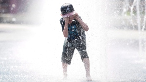 Seven-year-old Samuel Bedard from Quebec City runs through a water fountain as he beats the heat in Montreal, Monday, July 2, 2018. THE CANADIAN PRESS/Graham Hughes