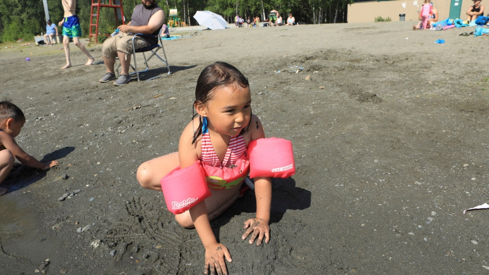 Milana Acuna, 5, makes a mud creation at the beach at Goose Lake as her father, Manny Acuna, looks on Friday, July 5, 2019, in Anchorage, Alaska. (AP Photo/Dan Joling)