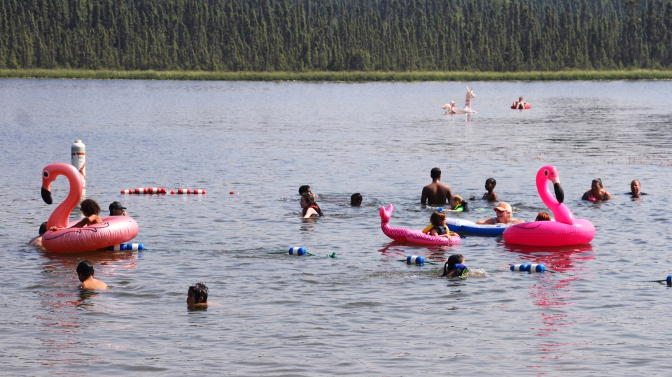 Children play with inflatable flamingos and other creatures at Goose Lake Friday, July 5, 2019, in Anchorage, Alaska. (AP Photo/Mark Thiessen)