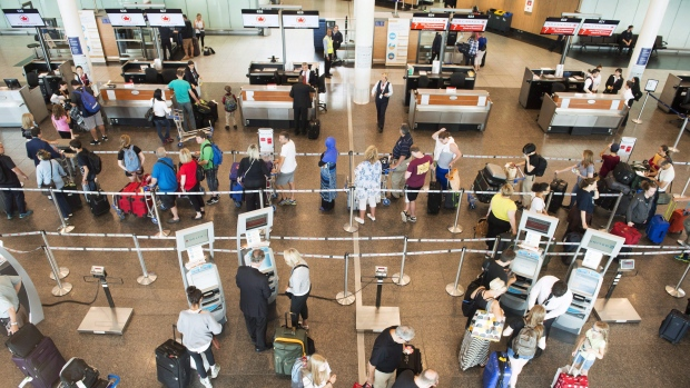 Passengers wait to check-in at Trudeau Airport on July 19, 2017 in Montreal. Canadian airlines are among the hundreds of carriers asking the Federal Court of Appeal to quash new rules around passenger rights. (THE CANADIAN PRESS/Ryan Remiorz)