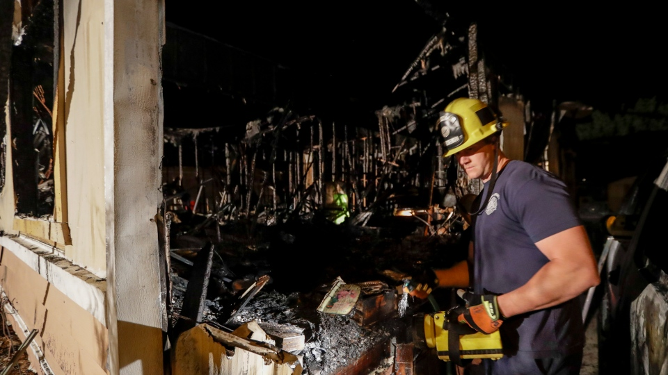A fireman looks over a home Saturday, July 6, 2019 that burned after a earthquake in Ridgecrest, Calif.Cali ( AP Photo/Marcio Jose Sanchez)