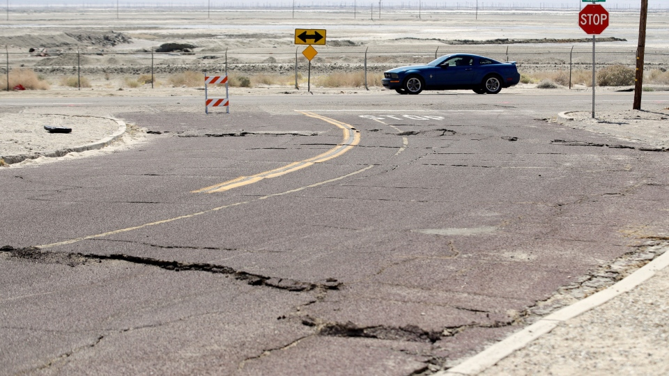 An earthquake-damaged street is seen Saturday, July 6, 2019, in Trona, Calif. (AP Photo/Marcio Jose Sanchez)